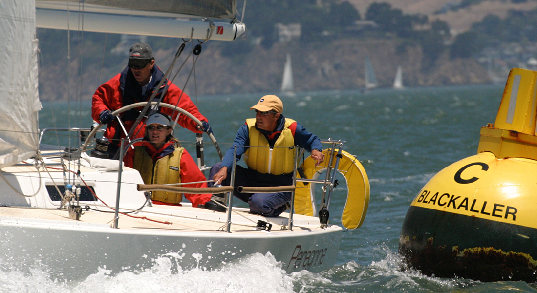 Three people sailing in choppy water